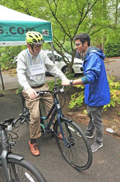 REVIEW PHOTO: VERN UYETAKE - Bob Sack gets some instruction from Anoop Herur-Raman as he getsready to go for ride on an electric bike at Sunday's EV Fair.