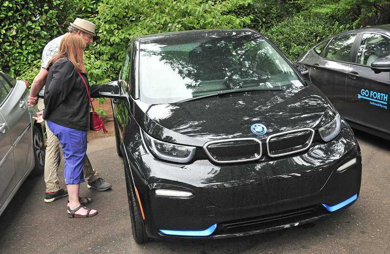 REVIEW PHOTO: VERN UYETAKE - Sheri and DickSchouten look over BMW's plug-in hybrid at the EV Fair on Sunday.