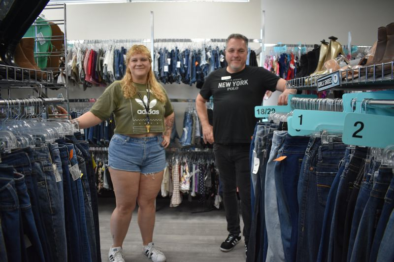 PMG PHOTO: SHANNON O. WELLS - Joanna Beall, Platos Closet district manager, and franchise owner George Merkl show off merchandise at their newly relocated used clothing store at 200 N.W. Burnside Road.