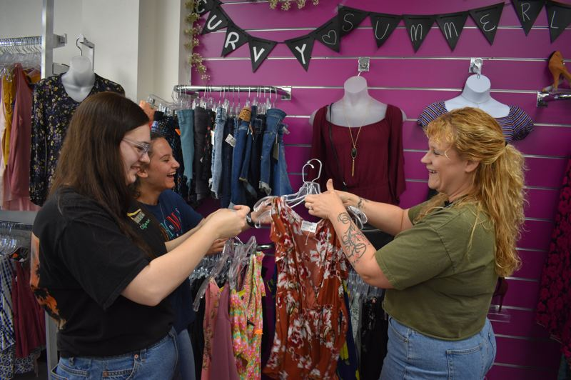 PMG PHOTO: SHANNON O. WELLS - From left, Platos Closet Shift Manager Brianna Beavers, buyer Karina Dziamidovich and District Manager Joanna Beall have fun while arranging merchandise on a recent Tuesday afternoon.