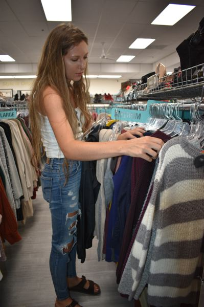 PMG PHOTO: SHANNON O. WELLS - Oregon City resident Megan Smith checks out shirts and sweaters in the young women's section of Platos Closet in Gresham.