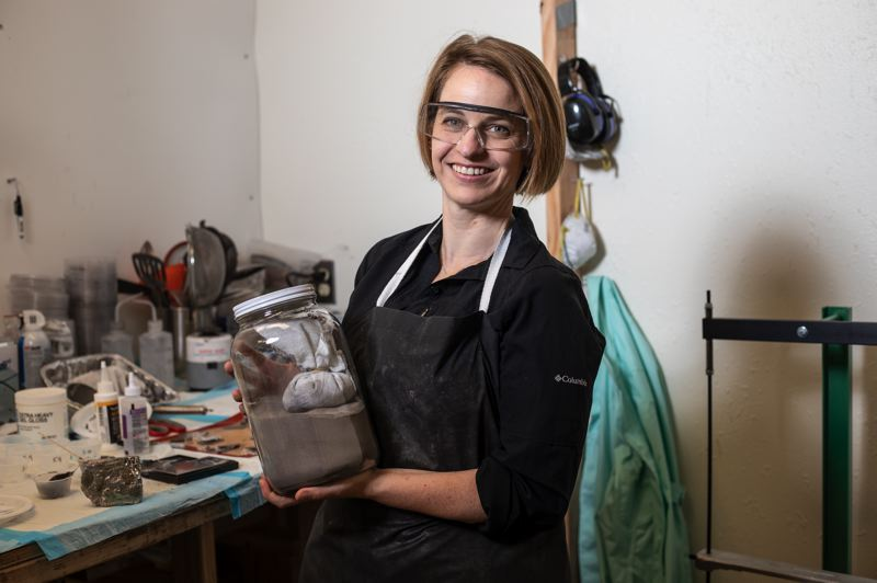 PMG PHOTO: JONATHAN HOUSE - Anna Brown holds a very heavy jar of bismuth in its particle form. As he company Stark Street Materials becomes part of the  Cascadia CleanTech Accelerator, Brown hopes to use bismuth instead of lead in x-ray shielding garments.