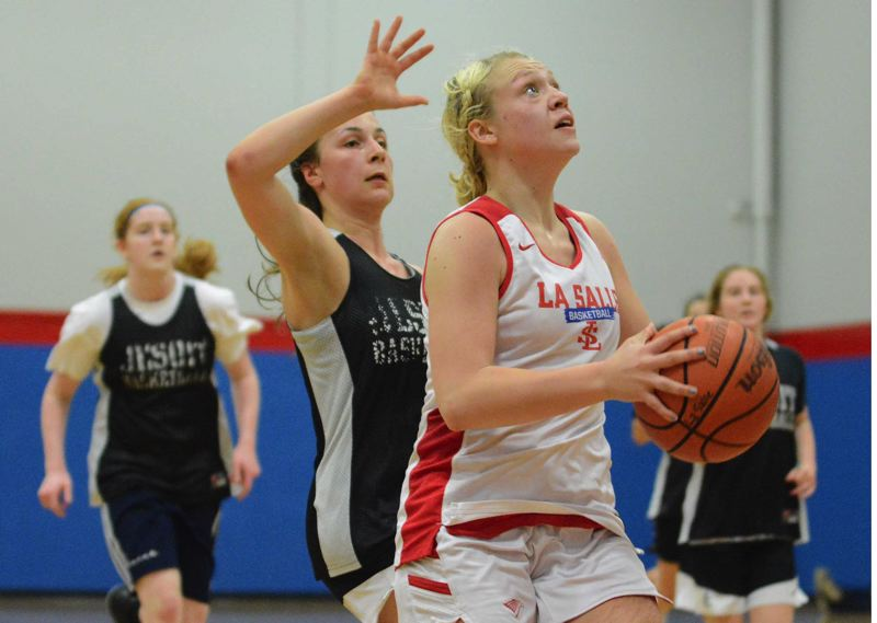 PMG PHOTO: DAVID BALL - La Salle Prep point guard Emily Niebergall beats a crowd of black shirts down the floor to finish a fast break during the Falcons 53-46 win over Jesuit at a summer tournament Saturday hosted by Centennial High.
