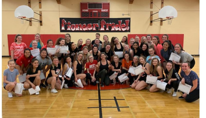 COURTESY PHOTO - Oregon City High School cheerleaders show off their calendars where they will mark their training for 10 minutes on days that they do not have practice at school with body-weight exercises.