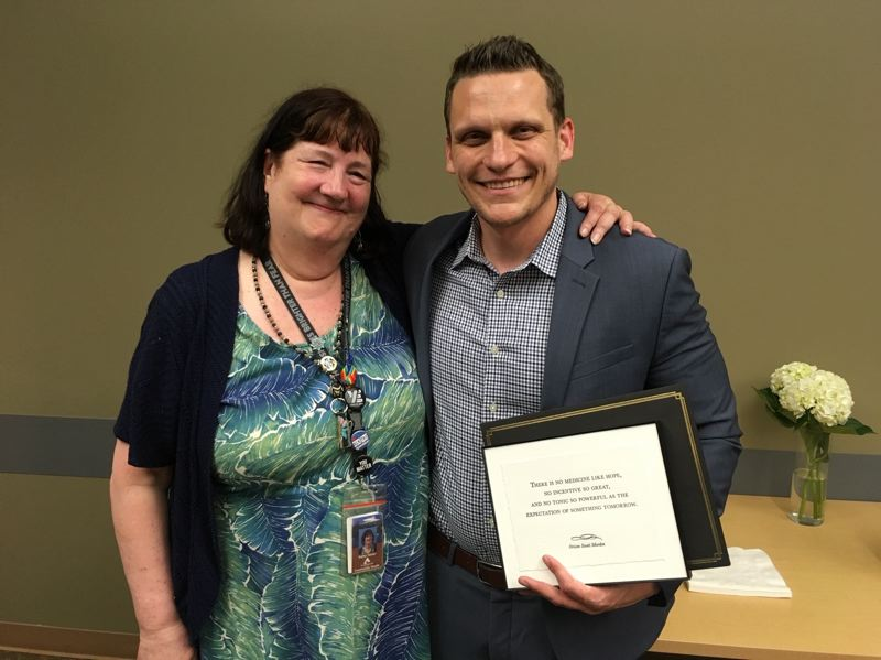 COURTESY PHOTO: OCSD - Kathy Turner of Clackamas County Behavioral Health presents an honor to Assistant Superintendent Kyle Laier for his teams long-term work on suicide prevention across the Oregon City School District.