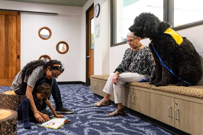 PMG PHOTO: CHRISTOPHER OERTELL - Tara Sinha, 4, reads Dr. Seuss' book 'One Fish, Two Fish' to Susan Carson's dog 'Ruben' during the Kids Read to Dogs event at the Hillsboro Brookwood Library.