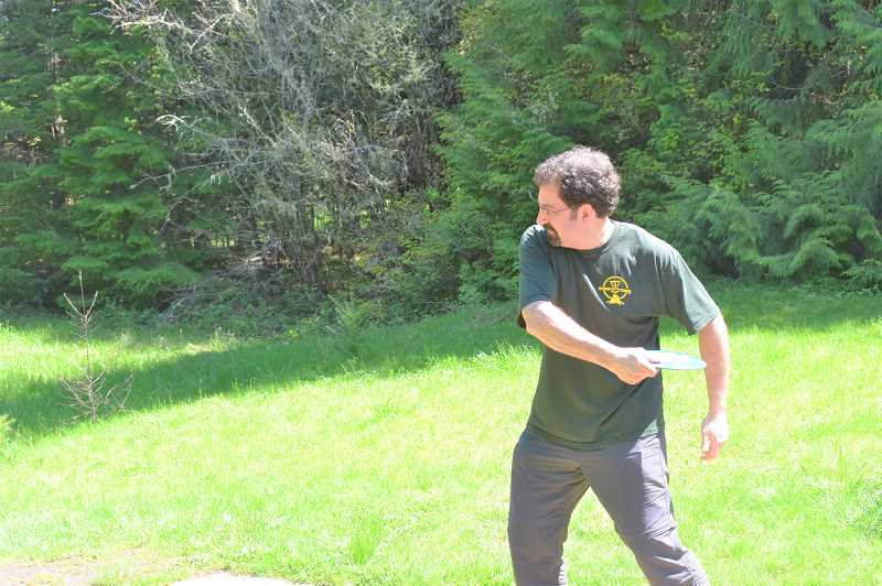 PMG PHOTO: EMILY LINDSTRAND - Patrick Buckley plays on the disc golf course at Milo McIver State Park.