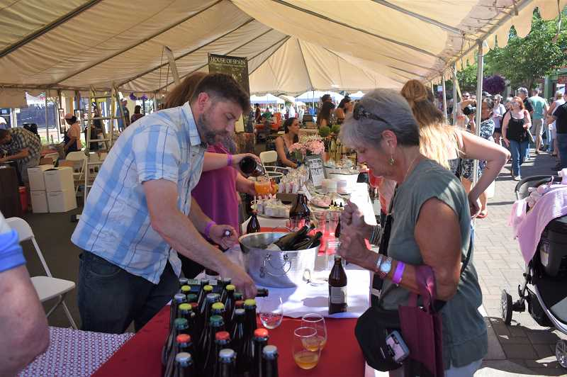 PMG FILE PHOTO: EMILY LINDSTRAND - Vendors serve beverages during last year's Estacada Uncorked event.