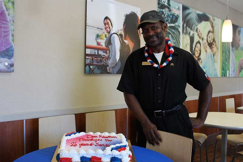 PMG PHOTO: AVA EUCKER - Deon Robertson smiles by a cake commemorating his diligent and loving work ethic.