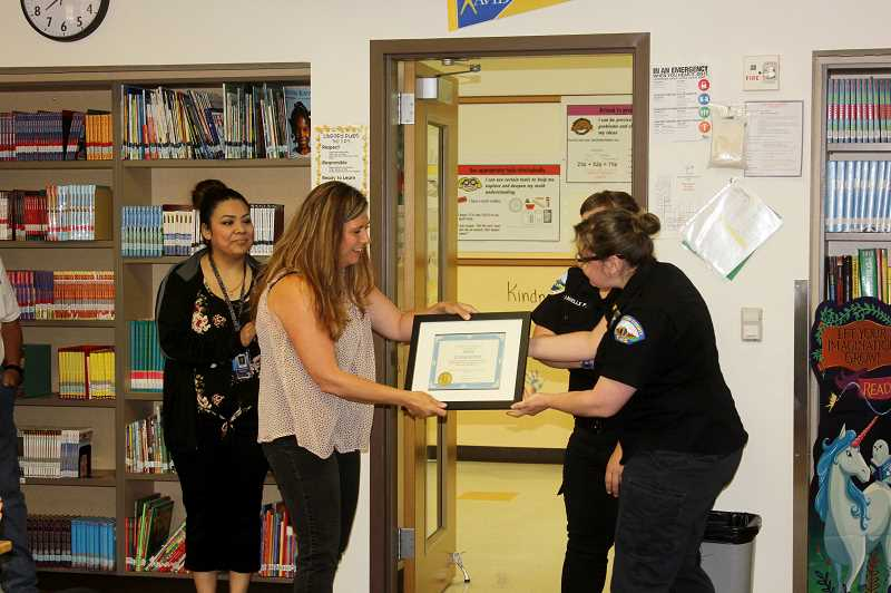DESIREE BERGSTROM/MADRAS PIONEER - Billie White, Buff Elementary School's principal, accepts an award from two EMS representitives, Daniell Peckham and Stephanie Swierkos, on behalf of the school after the school staff worked together to provide lifesaving CPR to a collapsed visitor, but also to keep the students calm and away from the incident.