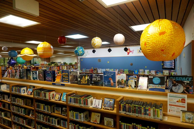 PMG PHOTO: CLAIRE HOLLEY - Andrea Milano and other library staff decorated the childrens library for the space-themed reading program.