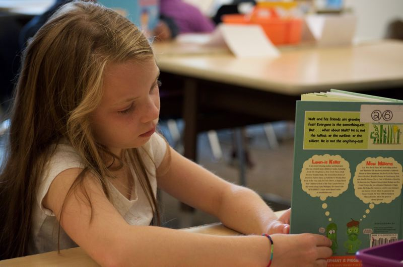 PMG PHOTO: CLARA HOWELL  - Third grader Amelia Beltz reads her book during the district's summer reading program.