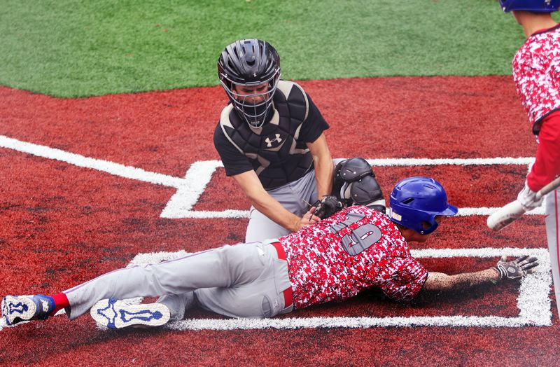 PMG PHOTO: DAN BROOD - Tualatin catcher Blake Jackson tags out La Salle's Patrick Raschio at home plate during the fourth inning of Thursday's game. The Wolves got a 3-0 victory.