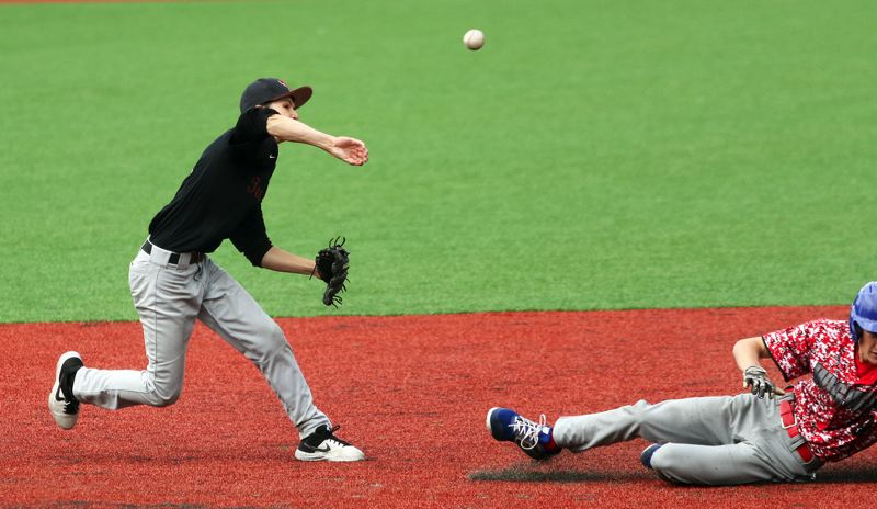 PMG PHOTO: DAN BROOD - Tualatin shortstop Xavier Otto (left) makes a throw to first base to complete a sixth-inning double play during the Wolves' 3-0 win over La Salle on Thursday.