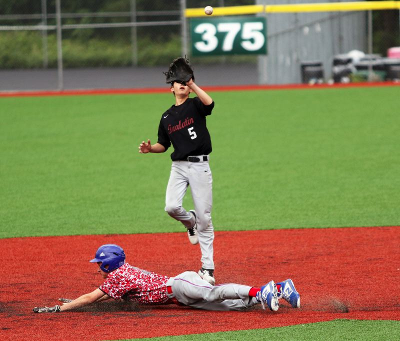 PMG PHOTO: DAN BROOD - Tualatin shortstop Xavier Otto (5) reaches for the ball as La Salle's Patrick Raschio slides to second base during Thursday's game. The Wolves won 3-0.