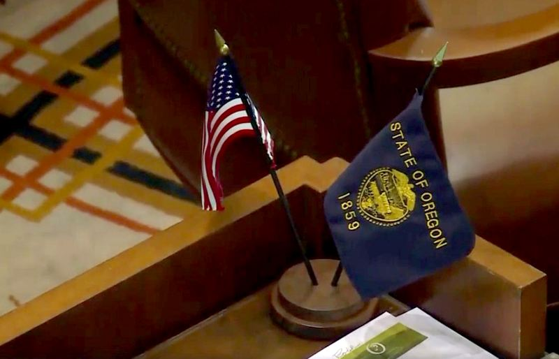 COURTESY PHOTO - State and federal flags sit on empty desks in the state Senate Friday, June 21. Republican senators have left the capital to block a vote on a controversial environmental bill.