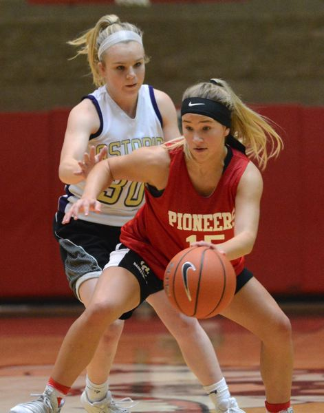 PMG PHOTO: DAVID BALL - Oregon Citys Kealy Kmetic moves past the center-court logo and Astoria defender Hailey OBrien.