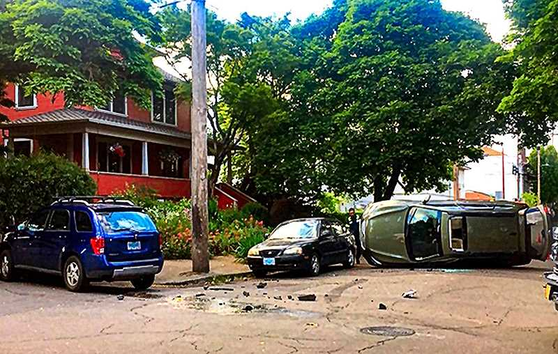 READER PHOTO - After being struck by a stolen car running a stop sign, the victim Subaru Outback rolled on its side. The responsible blue car at left was abandoned by the car thieves, who fled before police arrived.