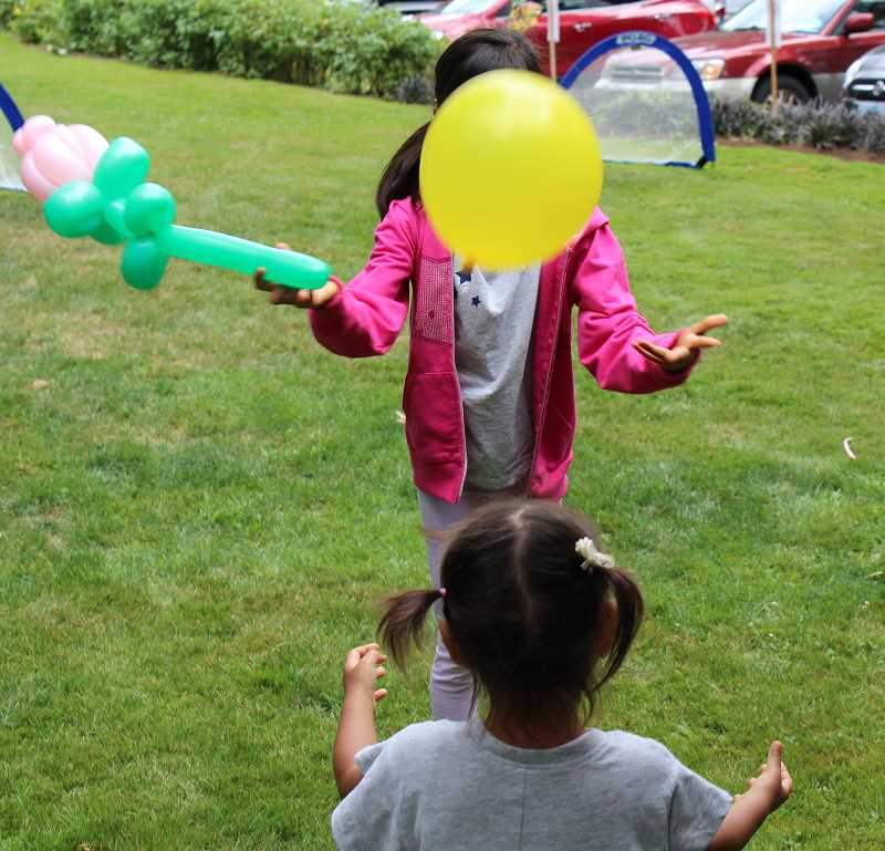 PMG PHOTO: AVA EUCKER - Sisters laugh while tossing balloons in Lower George Rogers Park