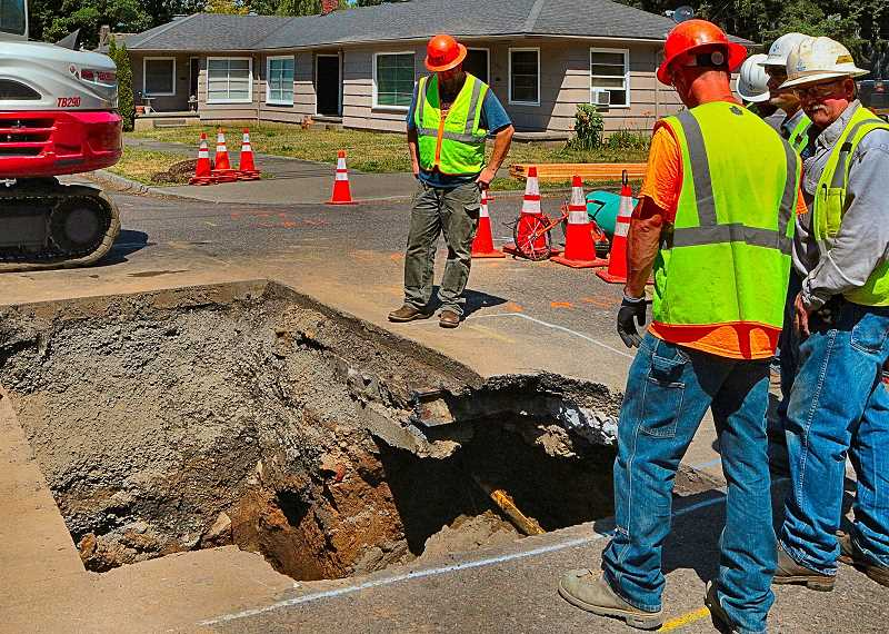 DAVID F. ASHTON - Shortly after the pavement caved in on June 12, PBOT workers used an excavator to open the hole that eventually become more than 18 feet deep, in order to reach and fix a broken sewer pipe.