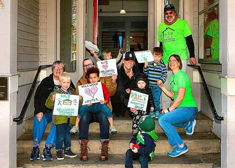 DAVID F. ASHTON - Showing support for the local effort to keep Sellwood Community Center open after August 31 are, from left: Gail Hoffnagle; Kelan Brandt; Amanda Demam, holding Julian, with his heart sign; Jasper Warner; Lisa Loffink; Simon Warner; and Clive Currin with mom Julie Currin. Standing behind is Jason Luedtke.