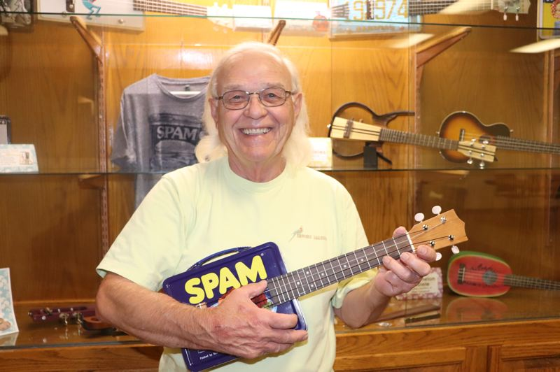 PHOTO BY TINA JOHNSON - Dan Caldwell strums a few bars on the Spam lunchbox ukulele that he made.