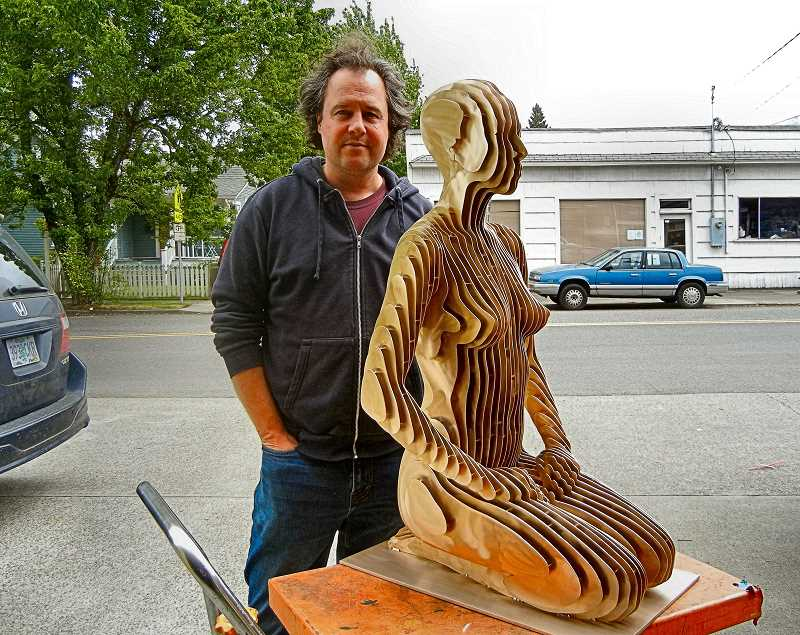 ELIZABETH USSHER GROFF - Artist and physicist Julian Voss-Andreae standing with Onah seated outside his Sellwood studio. Voss-Andreae and his team create nationally and internationally renowned sculptures.