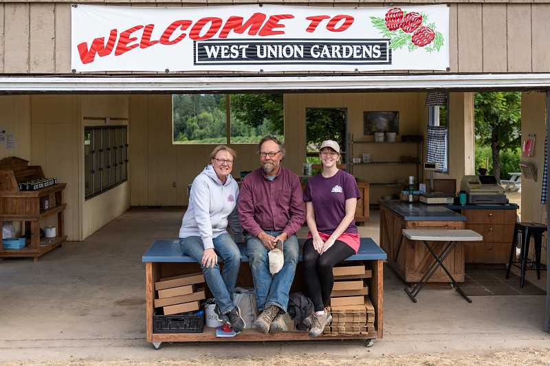 PMG PHOTO: CHRISTOPHER OERTELL - Cheryl Boden, husband Jeff and daughter-in-law Kady sit on a table at a farmstand at the West Union Gardens in Hillsboro.