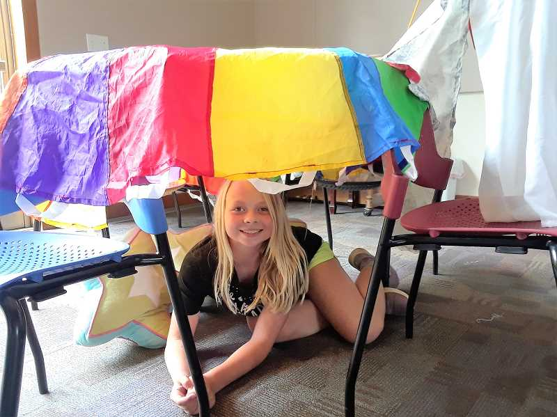 COURTESY PHOTO - Alexis Hibbert smiles from underneath her fort during an event at the Estacada Public Library on Wednesday, June 19.