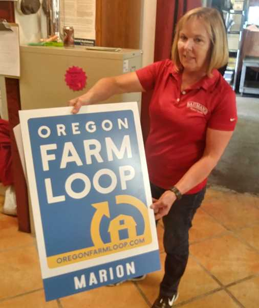 PMG PHOTO: JUSTIN MUCH - Barb Bauman shows the Marion County Farm Loop sign that adorns the 22 stops along Marion County Farm Loop, including Baumans Farm & Garden on Howell Prairie Road, Gervais.