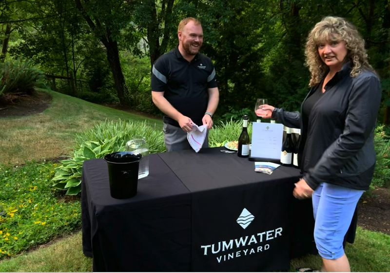 Eric Drinker from Tumwater Vineyard serves Tammy Owen at the 'Solstice Sip' event.