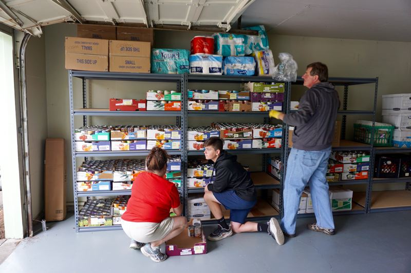 PMG PHOTO: CLAIRE HOLLEY - Hunger Fighters Oregon volunteers work to set up the food pantry at its new location