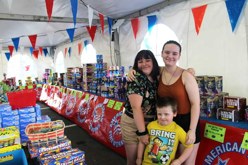 PMG PHOTO: KRISTEN WOHLERS - Band students Kat and Kassy Garrett, plus brother Kalib Spencer work the booth on June 26 and show off the loads of fireworks available. Purchases at this booth, located in the O'Reilly Auto Parts lot on 99E, will support the high school band and band students.