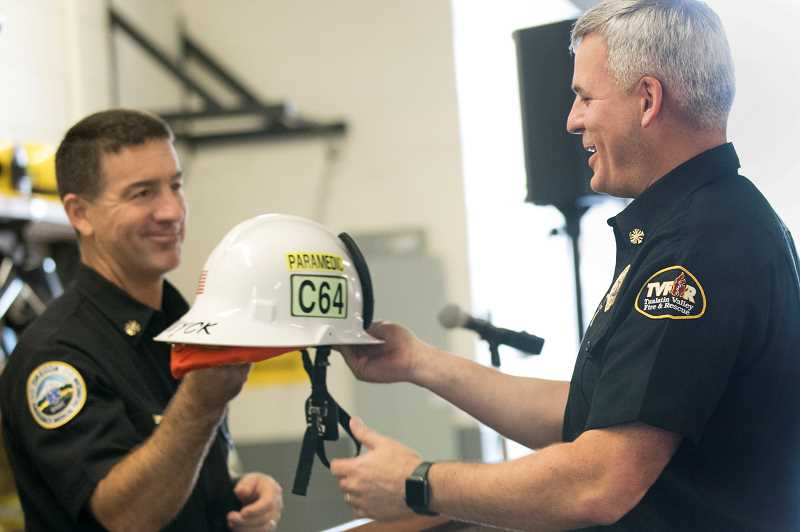 TIMES PHOTO: JAIME VALDEZ - Incoming TVF&R Fire Chief Deric Weiss, left, presents Chief Mike Duyck with his helmet, one of the few items firefighters are allowed to keep after leaving the service.
