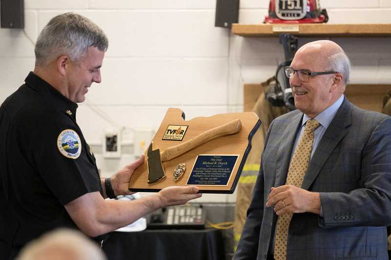 TIMES PHOTO: JAIME VALDEZ - Clark Balfour, left, vice president of the TVF&R Board, presents outgoing Chief Mike Duyck with a golden ax and badge plaque during a retirement open house held Thursday.