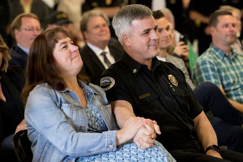 TIMES PHOTO: JAIME VALDEZ - Ann Duyck, wife of TVF&R Chief Mike Duyck, shares a laugh with her husband during a retirement presentation held Thursday morning in the bay of Tualatin Valley Fire and Rescue Station No. 51 in Tigard.