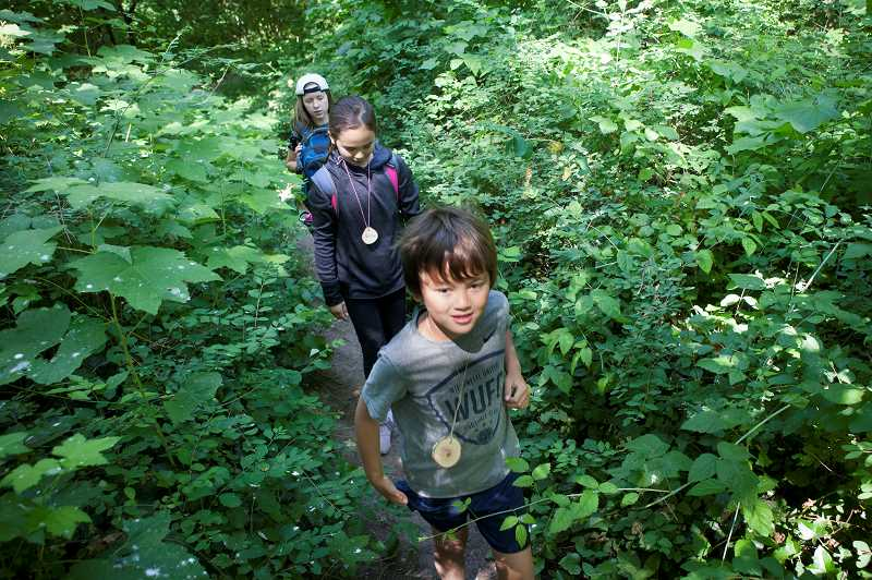 PMG PHOTO: JAIME VALDEZ - Enzo Owen, 8, leads Aisha Owen, 9, and Teagan Britt, 9, on a hike during EnviroCamp.