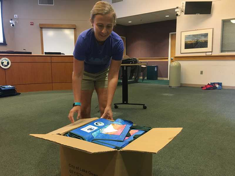 PMG PHOTO: SAM STITES - Sustainability Analyst Jenny Slepian opens a fresh box of reusable bags to be distributed throughout the community.