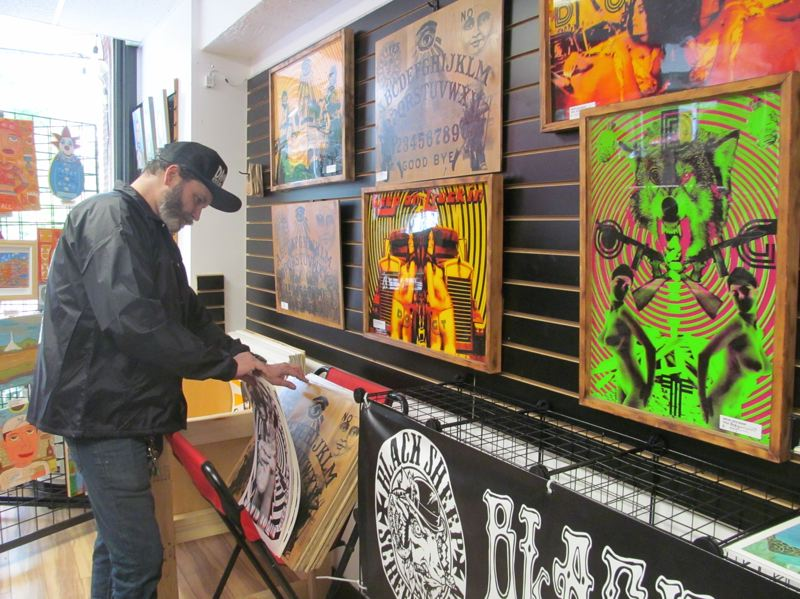 PHOTO BY ELLEN SPITALERI - Kyle Black, co-owner of Made in Milwaukie, leafs through his prints, suitable for framing. The wall in front of him displays his artwork with a psychedelic vibe.