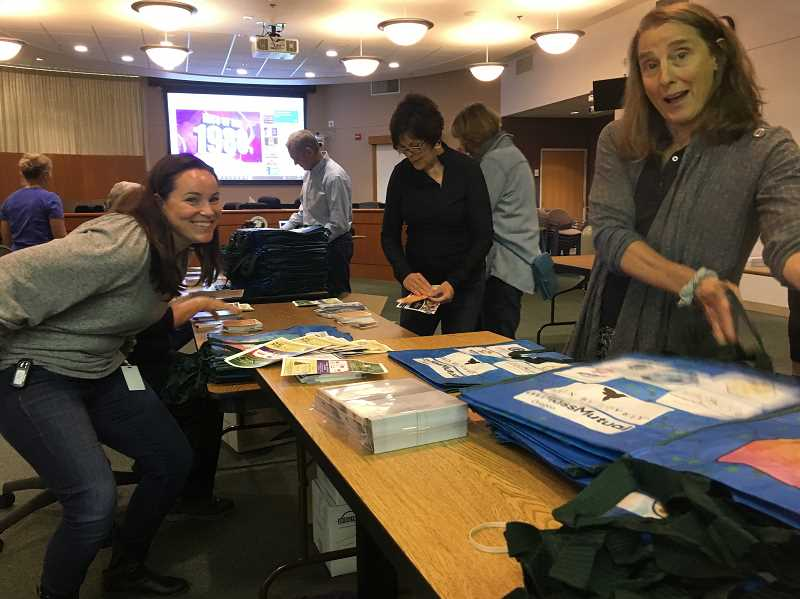 PMG PHOTO: SAM STITES - Deputy City Recorder Kari Linder (left) City Recorder Anne-Marie Simpson (center) and LO Sustainability Network co-founder Dorothy Atwood (right) put together packets of info with reusable bags to be distributed this weekend.