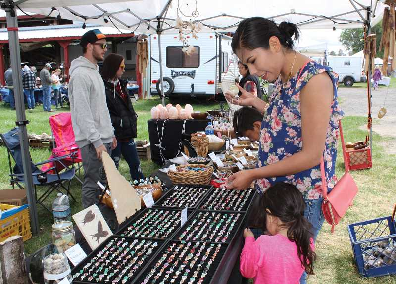 HOLLY M. GILL/MADRAS PIONEER - Kirstie Morrison, of Madras, with daughter, Mila, 3, admires the jewelry at a booth set up by Dalton Early, of DME Fossils and Stones, of Bend.