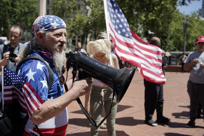PMG PHOTO: KIT MACAVY - Kerry Hudson, an activist who frequently attends Patriot Prayer events, holds a mega-phone during a rally in Portland on June 29.
