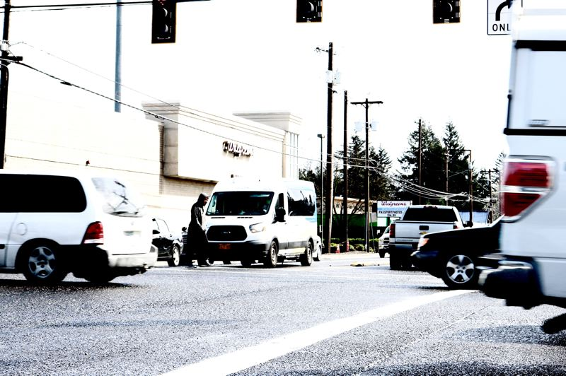 PMG PHOTO: ZANE SPARLING - A man crosses the street while cars whizz by at the corner of Powell Boulevard and 122nd Avenue in Southeast Portland.