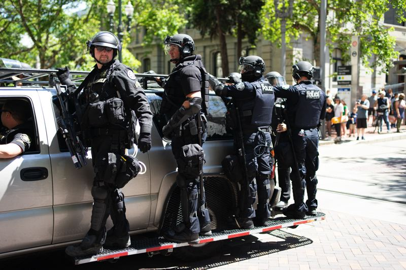 PMG PHOTO: KIT MACAVOY - Portland police officers decked out in riot gear ride on a truck during a violent protest in Portland on Saturday, June 29.