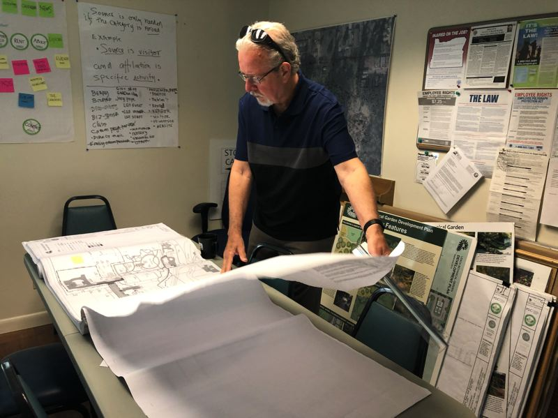 PMG PHOTO: STEPHANIE BASALYGA - David Porter, executive director of Leach Garden Friends, looks over the Upper Garden Project plan for Leach Botanical Garden. The first phase of the project is slated to begin this summer.