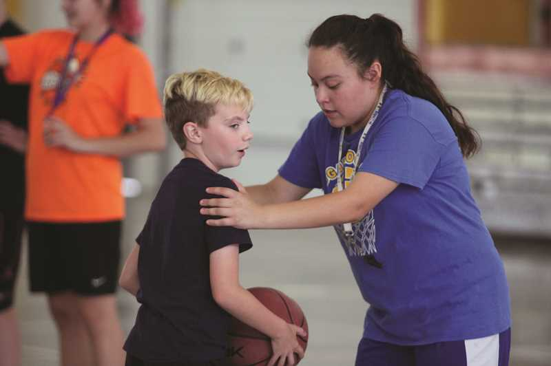 PMG PHOTO: PHIL HAWKINS - Gervais junior Marisol Ayala and her basketball teammates help conduct the Cougars' annual Hoop Camp each summer.