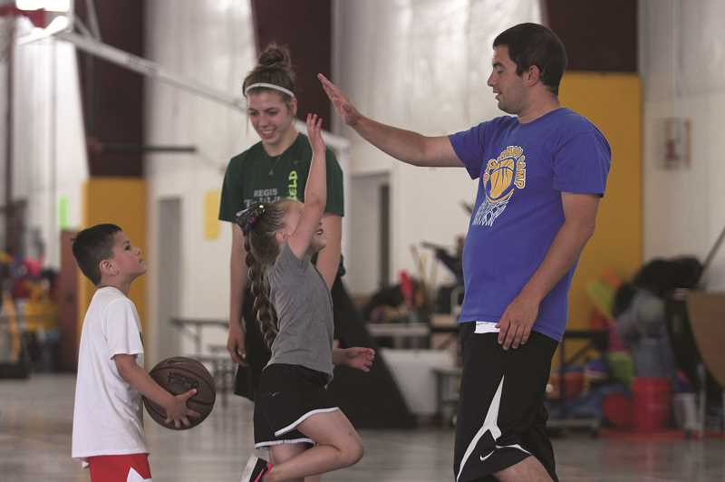 PMG PHOTO: PHIL HAWKINS - Gervais head coach Kyle Buse and junior Katie Hanson play a little 2-on-2 between sessions of the Cougar Hoop Camp last week. The event has been has grown over the years at Gervais High School, bringing in young athletes from the surrounding region to play and learn new basketball skills.