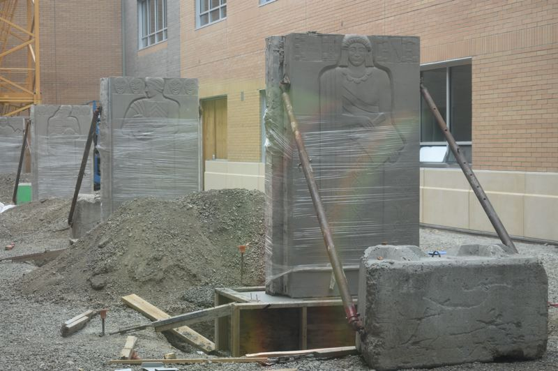 PMG PHOTO: TERESA CARSON - The four bas relief Art Deco-style muse sculptures that were above the entrance to the high schools auditorium were removed and restored and are being installed in a courtyard of the new classroom wing.
