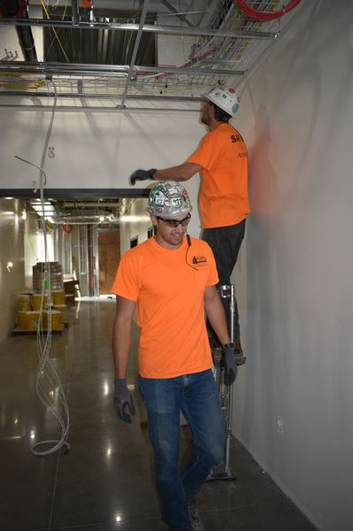 PMG PHOTO: TERESA CARSON - These workers are working on the dropped grid ceiling.
