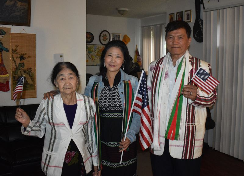 PMG PHOTO: TERESA CARSON - New citizens Vung Man Cin, Niang Suan Cing and Thang Kaw Mang, in ethnic Zomi clothing, show off their American flags.